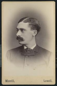 Portrait of young mustachioed man in a coat