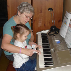 Older adult teaching child to play piano.
