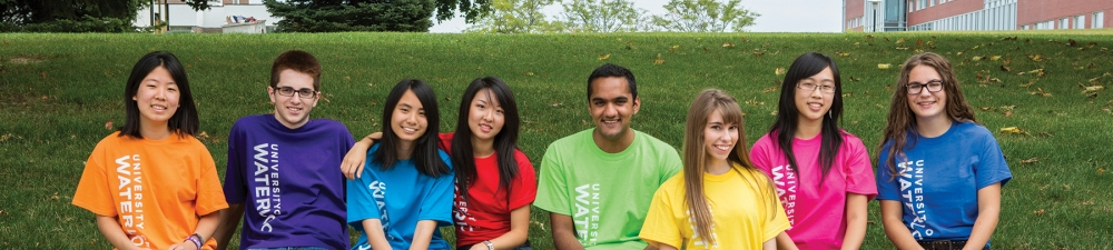 Students smilng wearing their faculty colours