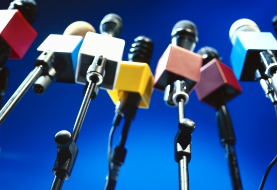 A line of microphones at a press conference