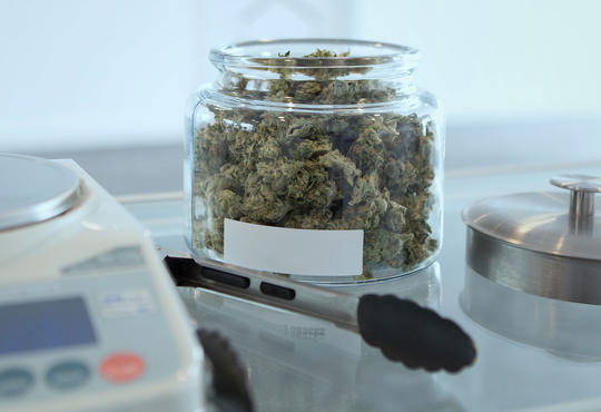 jar of cannabis bud beside a scale