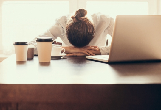 woman with her head down on her desk in defeat