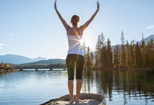 Woman with raised arm by a lake to show victory and recover