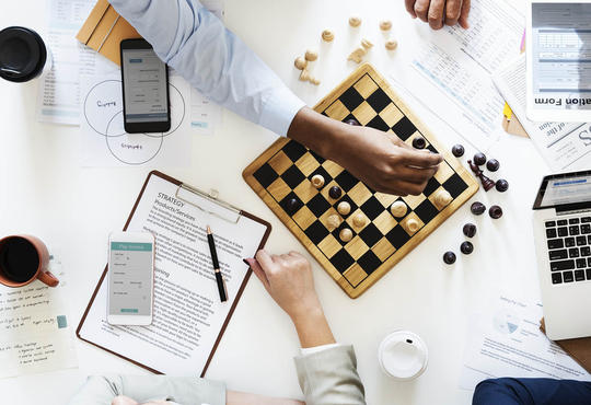 Diverse people around a table playing chess