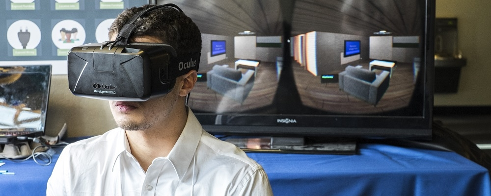 student stands with oculus rift enabled in front of two monitors to show the use of the virtual reality tool.