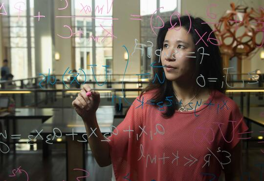 woman standing in front of a clear white board solving an equation