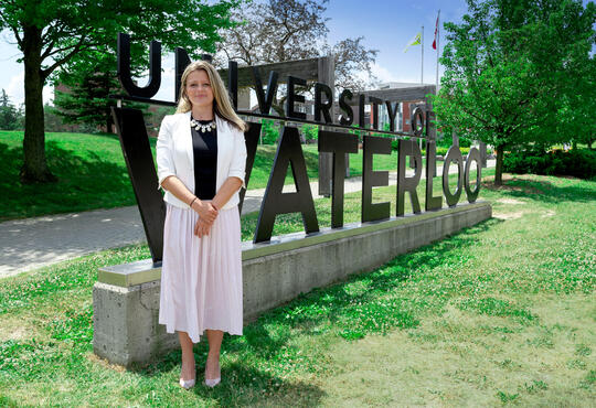 woman in a white and black dress standing in front of UWaterloo entrance sign