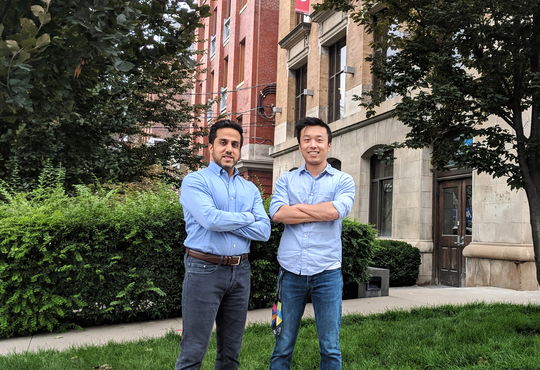 Henry Shi and Hussein Fazal stand smiling together outdoors