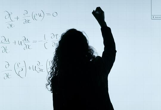Back of woman with long hair writing on a white board
