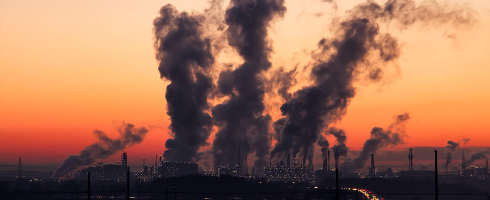 Several smoke stacks working against a sunset sky