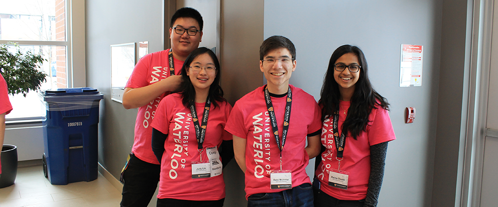 Four math ambassadors in pink t-shirts smile at the camera during March Break Open House