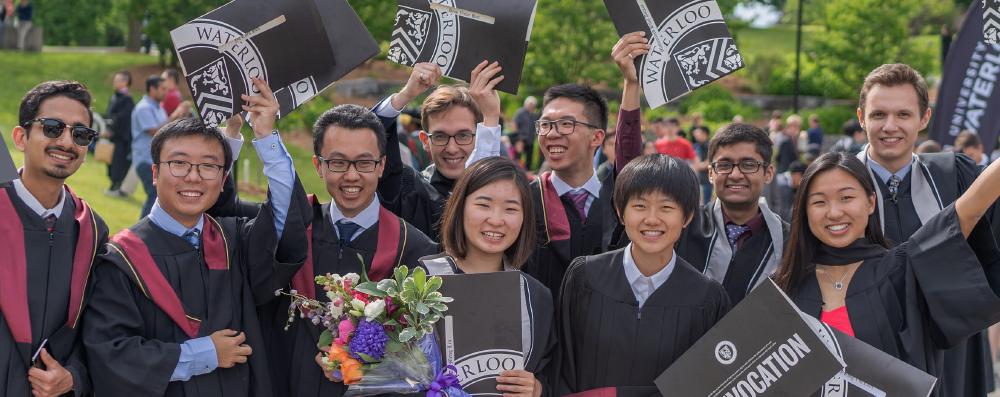 Group of graduating students waving diplomas