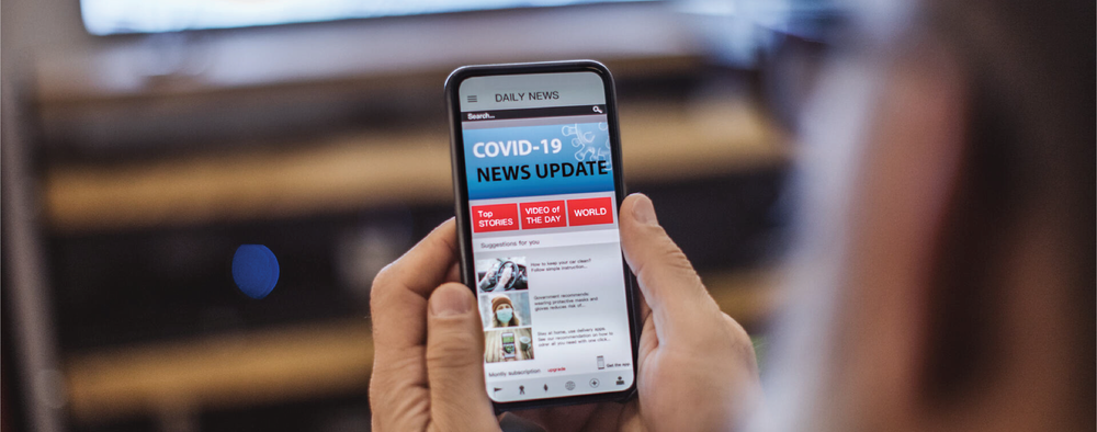 Phone being held with COVID-19 news update on screen