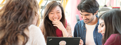 Students smiling and laughing at a laptop