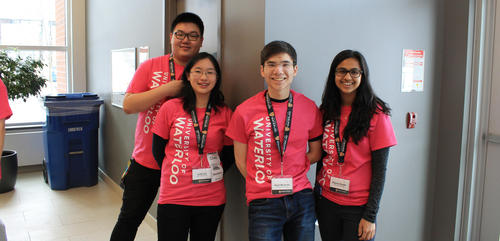 Four students in pink t-shirts welcome guests at an Open House
