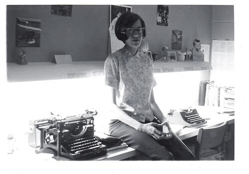 Young woman sitting on a desk beside a typewriter
