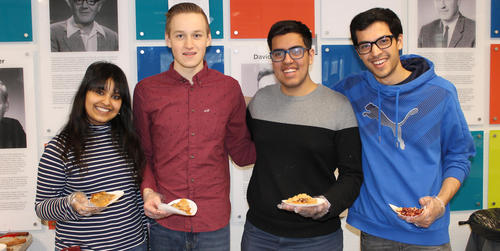 Four students smile with their slices on Pi Day