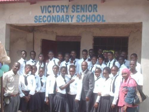 Group photo outside Victory Senior Secondary School entrance.
