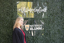 A female student smiles next to Waterloo Grad sign