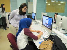 A teacher helps a student in a computer lab