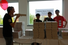 Volunteers selling pizza at an open house event.