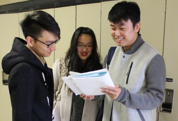 three students reading papers