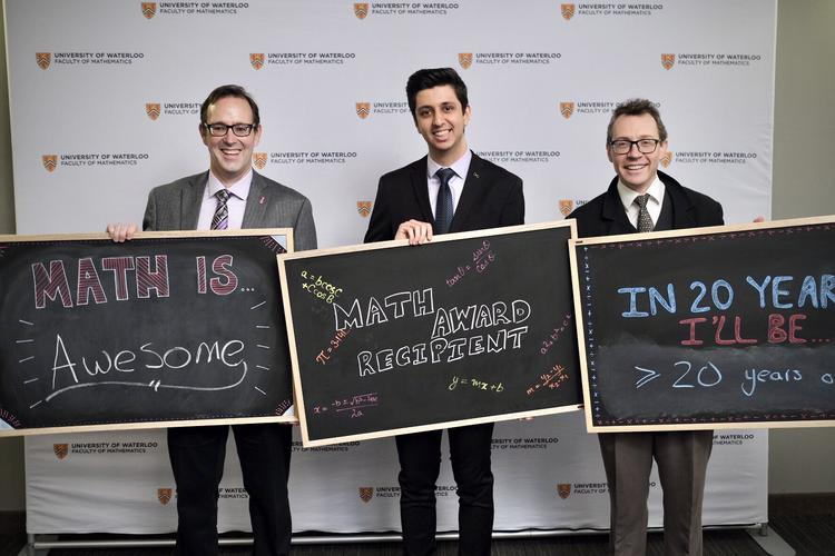 3 men standing side by side holding chalkboards