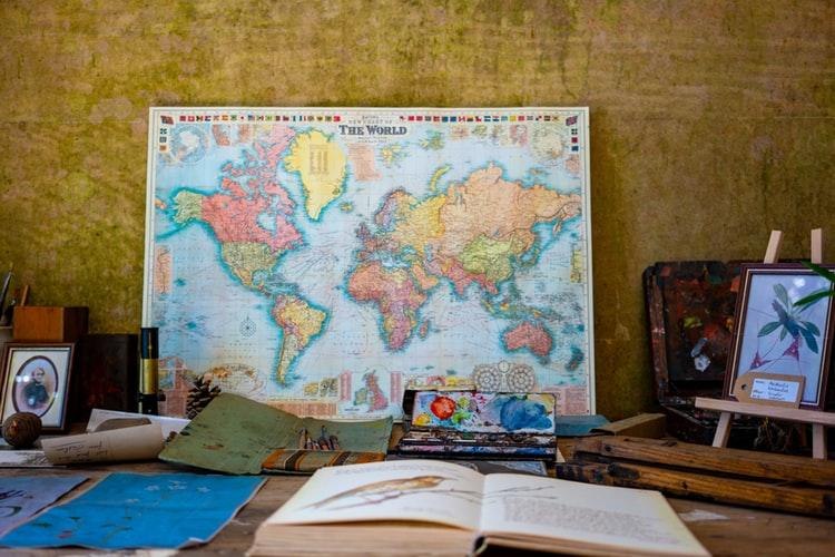 world map poster near book and easel