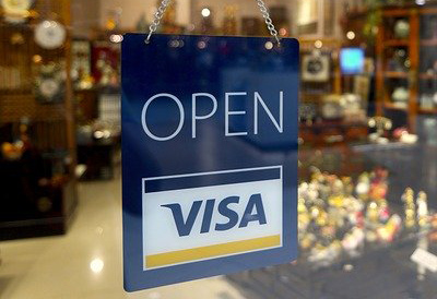 Store front with a VISA n Open sign