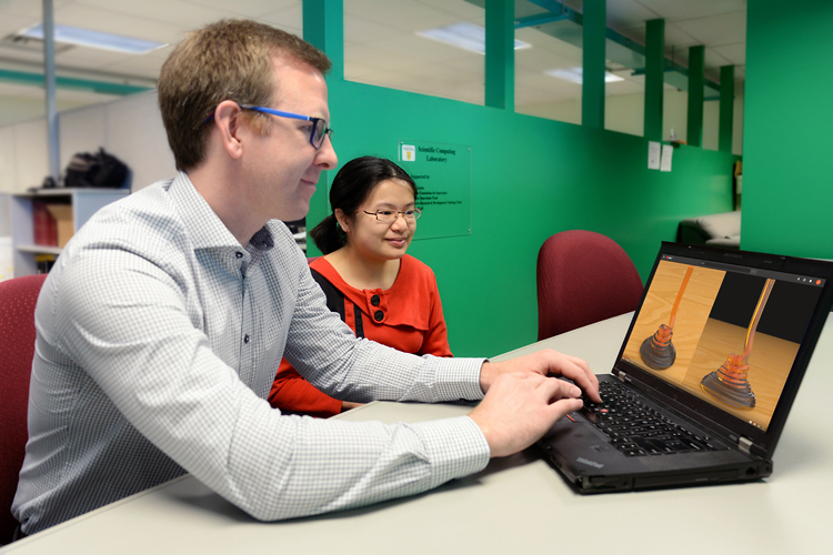 Professor Christopher Batty and his master's student Jade Marcoux-Ouellet watch a computer animation of honey coiling that he, E