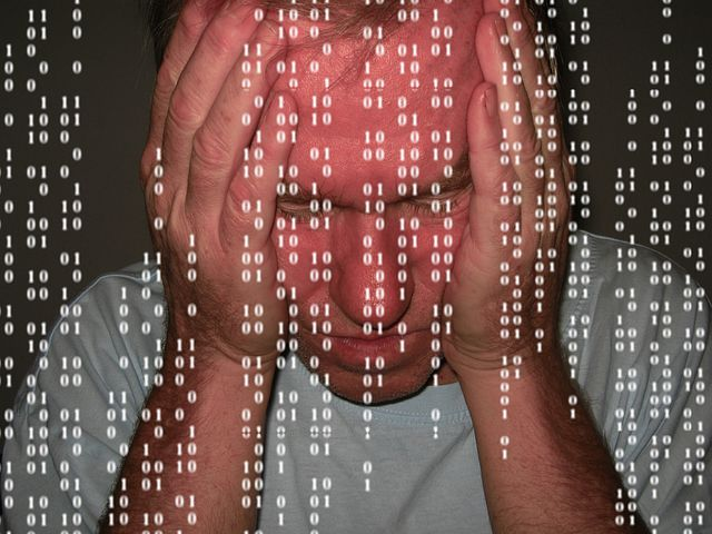 Man looking frustrated with computer codes in the foreground