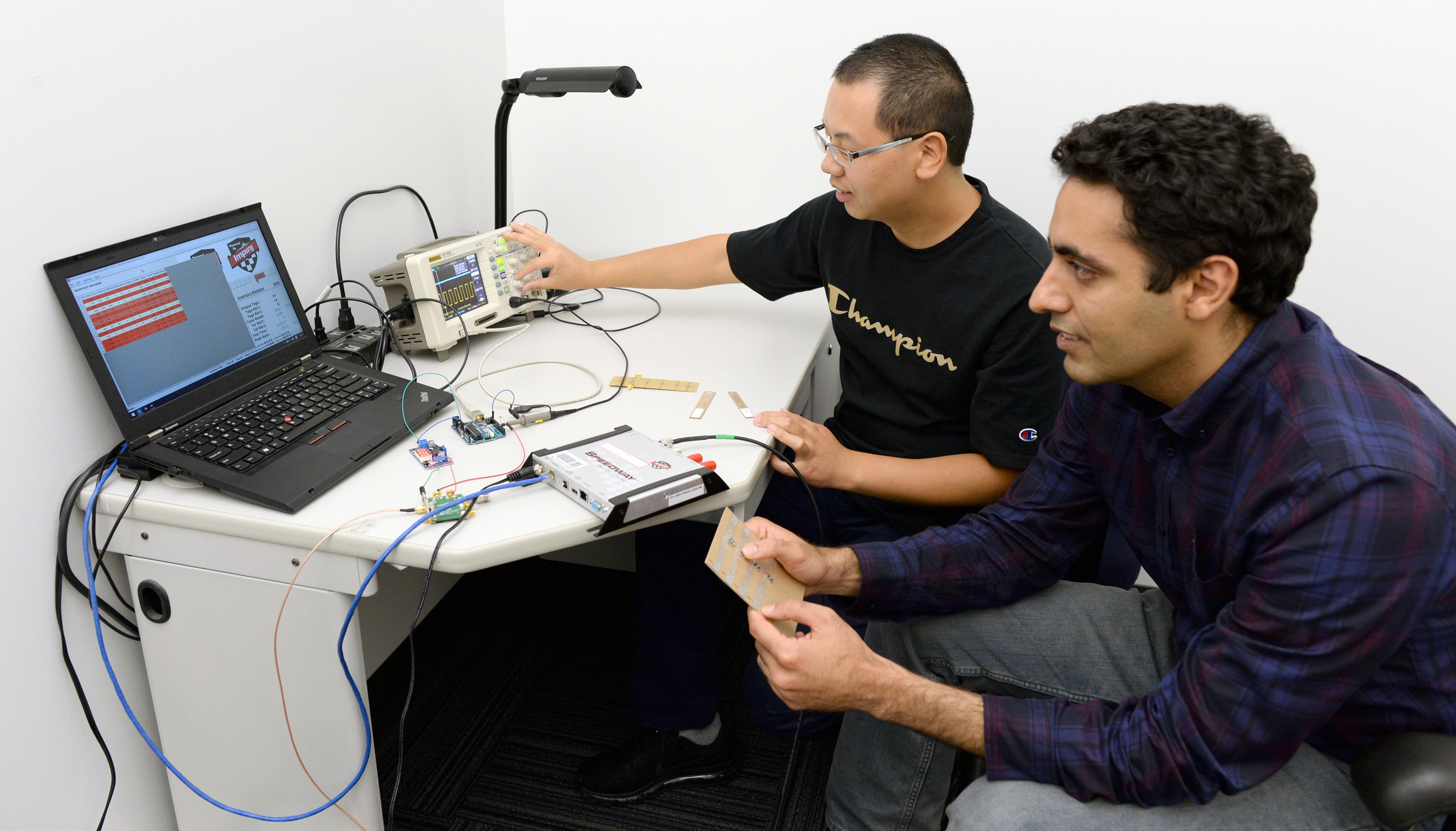 Wang and Abari demonstrate their Internet of Things hack at a computer.