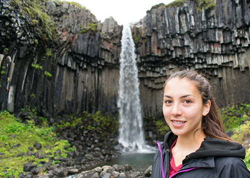Lizz Webb standing in front of a waterfall