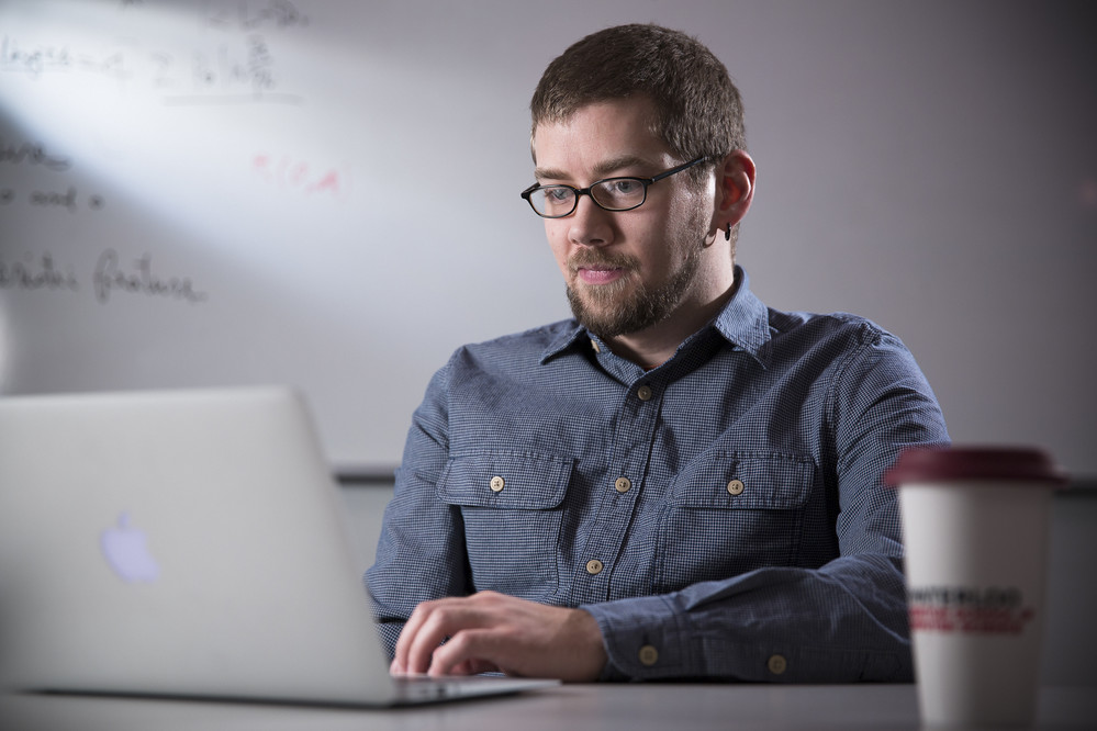 male graduate student on laptop