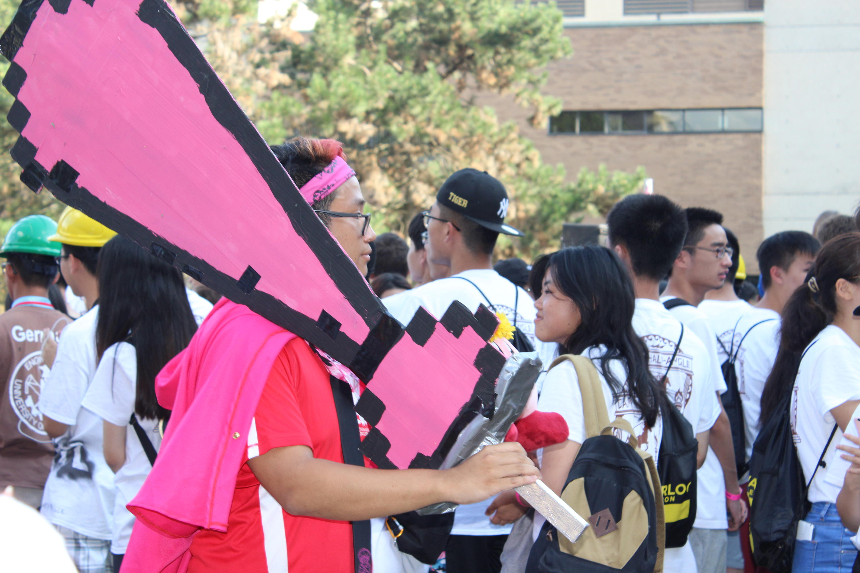 Orientation leader carrying large pink tie sign