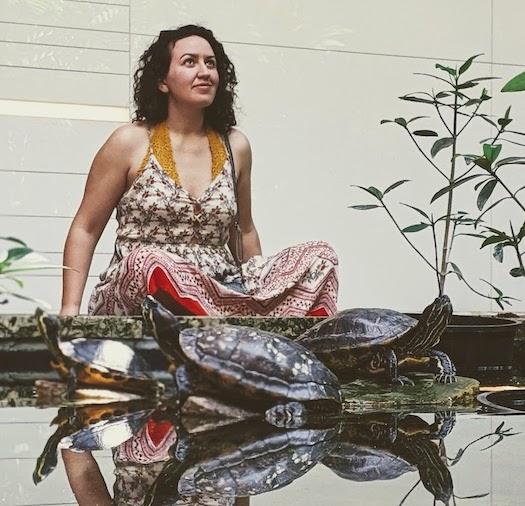 Adina Goldberg seated behind a pond with turtles