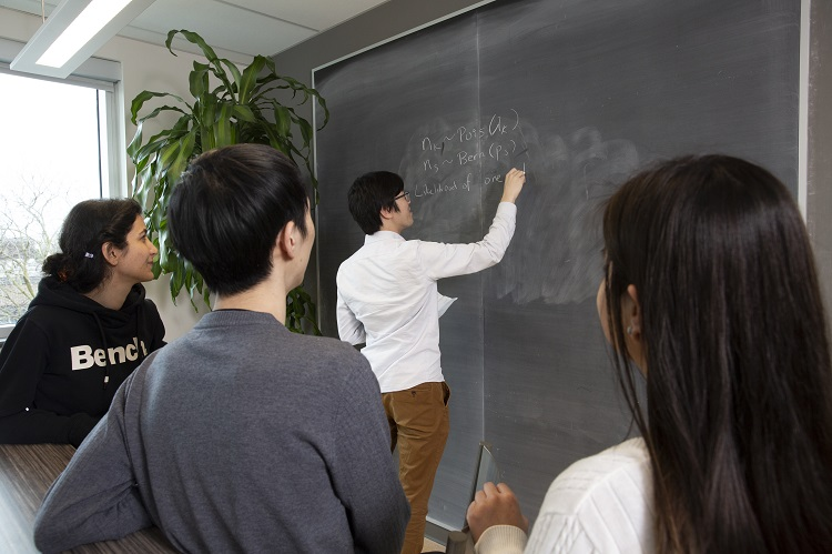 Statistics graduate students working at a blackboard