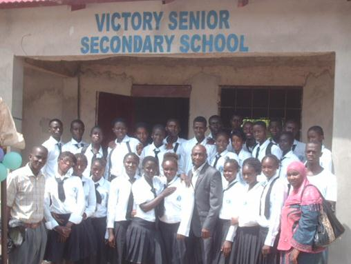 Group photo outside Victory Senior Secondary School entrance.
