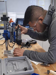 Student focused on working with a Dremel 3000 rotary tool