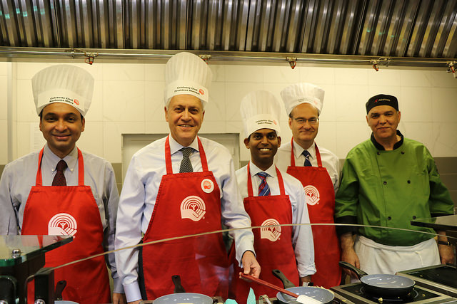 Sushanta Mitra and other faculty dressed as chefs behind a cooking line.