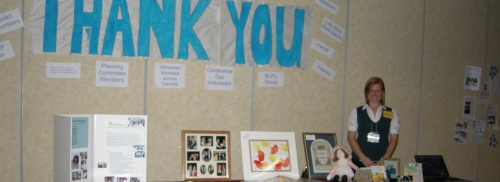 "Young woman standing beside a display of books and pictures with a large ""Thank You"" sign on the wall behind her"