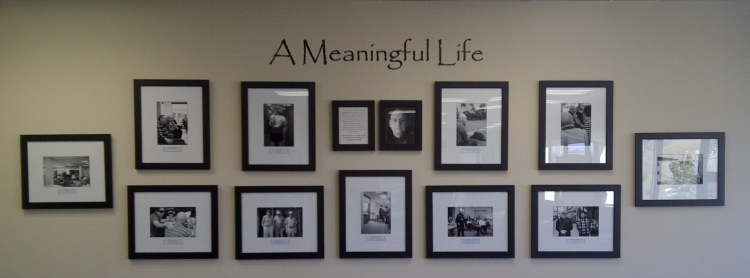 "A set of black and white photos hanging on a wall with the words ""A Meaningful Life"" in black letters above the grouping"