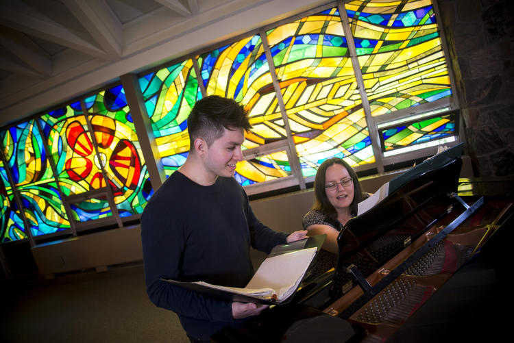 A music student and teacher laugh as they practive in the Grebel Chapel