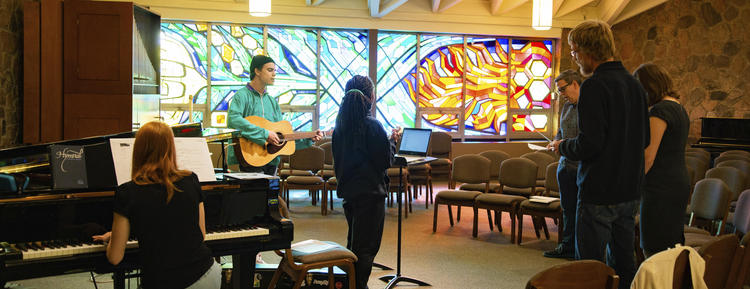 Three worship apprentices practice singing with mentors in the Grebel chapel