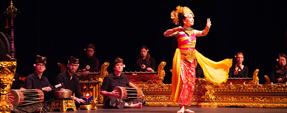 A dancer on stage performs with the Balinese Gamelan