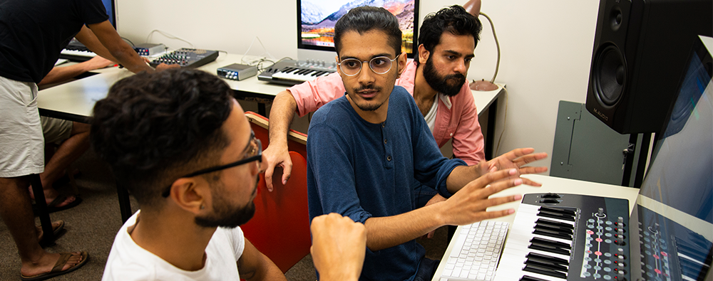 students in the digital music lab discuss over an electronic paino