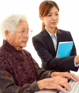 Elderly woman using a computer, with assistance from young woman.