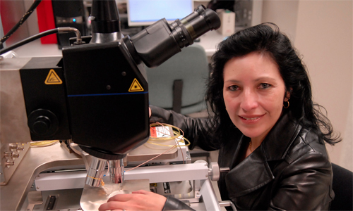A dark-haired woman sits at a microscope in a lab.