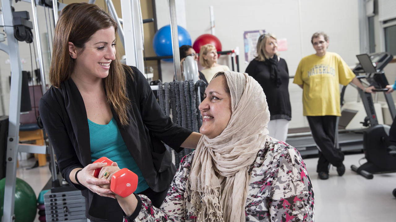 student helping woman with fitness training