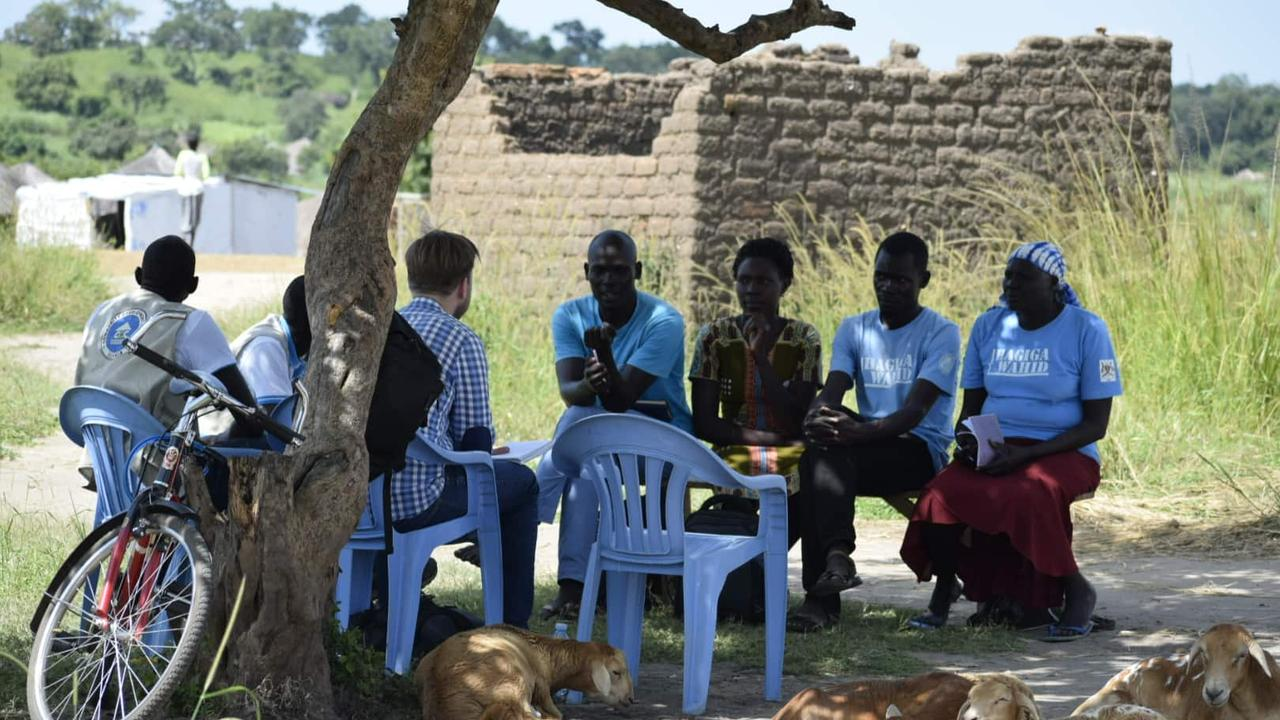 Christopher speaking with local villagers